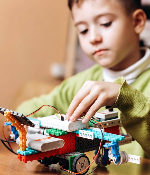 child experimenting with a robot he made during robotics class