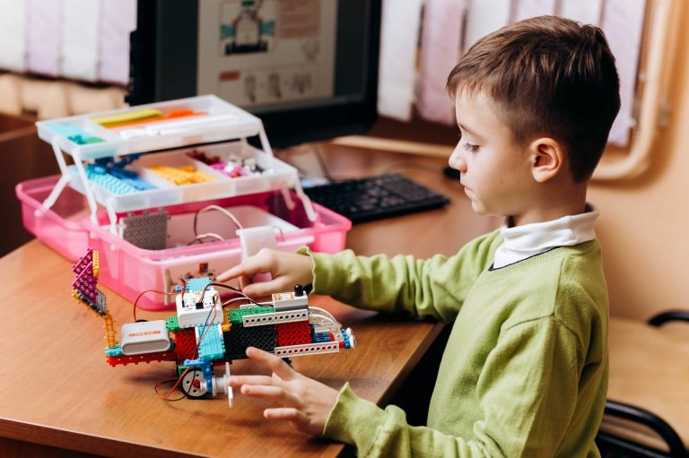 Diligent boy dressed in green sweater sits at the desk with computer and makes the robot from the